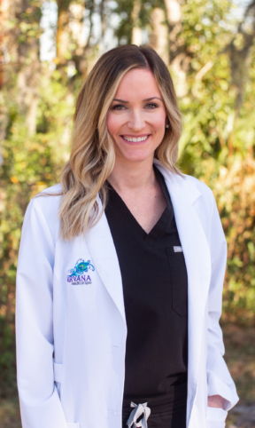 Member of the Nirvana Medical Spa Team, Kaylee stands in her white coat and black crubs